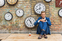 坐在有时钟的墙壁附近的衣服的人 免版税库存照片