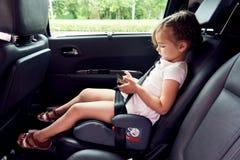 坐在有智能手机的一辆汽车的小女孩 免版税库存照片
