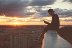 坐在有智能手机的屋顶边缘的年轻勇敢的人 免版税库存照片