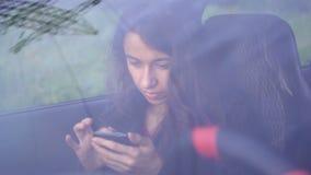 坐在有智能手机的汽车的美丽的少妇 股票录像