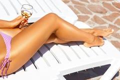 坐在有杯的轻便马车休息室的妇女酒 免版税库存照片