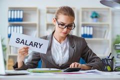 坐在有消息的办公室的女实业家 免版税库存照片