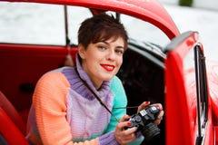 坐在有照相机的汽车的花姑娘 女性摄影师 旅行的概念 库存图片