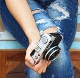 坐在有照相机的被撕毁的牛仔裤的时髦的妇女 时尚,生活方式,秀丽,衣物 免版税库存图片