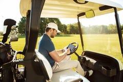 坐在有片剂的一辆高尔夫车的年轻人 库存图片