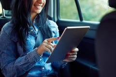 坐在有片剂计算机的一辆汽车的妇女 图库摄影