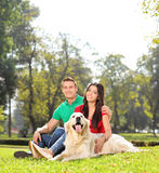 坐在有狗的公园的年轻夫妇 免版税库存照片