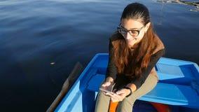 坐在有电话的一条小船的美女 慢的行动 在水的美丽的波浪 股票视频