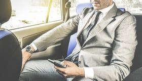 坐在有电话的出租车的年轻英俊的商人 免版税库存图片
