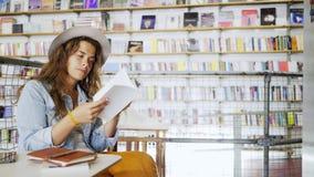 坐在有电话的图书馆里的女孩在手上 股票视频