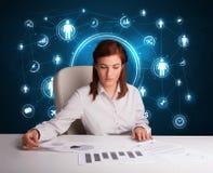 坐在有社会网络图标的服务台的女实业家 库存照片