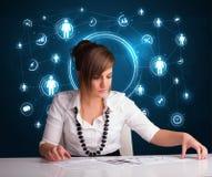 坐在有社会网络象的书桌的女实业家 免版税库存照片