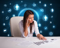 坐在有社会网络象的书桌的女实业家 库存照片
