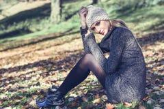坐在有秋天颜色的一个公园的年轻白肤金发的妇女 免版税图库摄影
