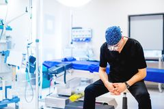坐在有空的桌的手术室的专业外科医生 库存图片