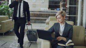 坐在有笔记薄和便携式计算机的扶手椅子的白肤金发的女实业家,当与行李的通过时走的商人 股票视频