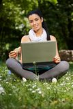 坐在有膝上型计算机微笑的公园的俏丽的女孩 库存照片