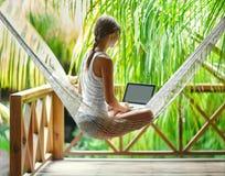 坐在有膝上型计算机的一个吊床的少妇在一热带resor 免版税库存照片