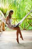 坐在有膝上型计算机的一个吊床的少妇在一热带resor 库存图片