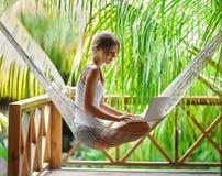 坐在有膝上型计算机的一个吊床的少妇在一热带resor 库存照片