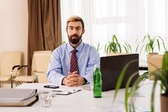 坐在有膝上型计算机的一张书桌的商人 库存照片