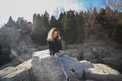 坐在有膝上型计算机的公园的美丽的女孩和在阳光沐浴 免版税库存图片