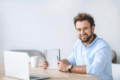坐在有膝上型计算机的工作场所和在手中指向空白的笔记本的商人 免版税库存照片