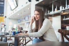 坐在有膝上型计算机的自助食堂和使用手机的少妇 库存图片