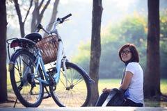 坐在有自行车的公园在早晨使用为helathy生活和放松在假日和假期的亚裔妇女 免版税图库摄影