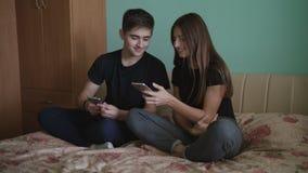 坐在有蓝色墙壁的一间屋子里和使用与一个手机的年轻人和美女 股票视频