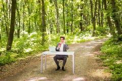 坐在有谈的便携式计算机和的咖啡的办公桌的商人手机在绿色森林公园 事务 免版税库存图片