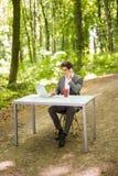 坐在有谈的便携式计算机和的咖啡的办公桌的商人手机在绿色森林公园 事务 库存照片