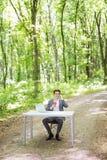 坐在有谈的便携式计算机和的咖啡的办公桌的商人手机在绿色森林公园 Busine 库存图片