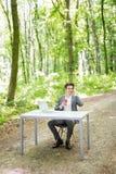 坐在有谈的便携式计算机和的咖啡的办公桌的商人手机在绿色森林公园 Busine 库存照片