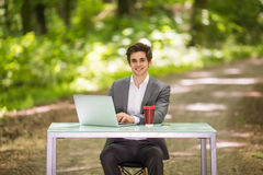 坐在有谈的便携式计算机和的咖啡的办公桌的商人画象在绿色森林同水准的手机 图库摄影