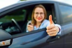 坐在有赞许的一辆汽车的年轻愉快的妇女 库存图片