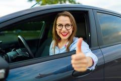 坐在有赞许的一辆汽车的年轻愉快的妇女 库存照片