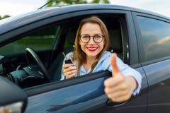 坐在有赞许的一辆汽车的年轻愉快的妇女 免版税库存图片