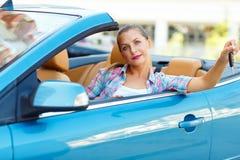 坐在有钥匙的一辆敞篷车汽车的年轻俏丽的妇女 库存照片