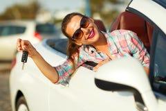 坐在有钥匙的一辆敞篷车汽车的年轻俏丽的妇女 免版税库存图片