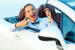 坐在有钥匙的一辆敞篷车汽车的年轻俏丽的妇女 免版税图库摄影