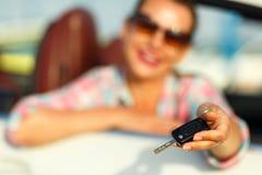 坐在有钥匙的一辆敞篷车汽车的年轻俏丽的妇女 库存图片