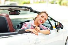坐在有钥匙的一辆敞篷车汽车的年轻俏丽的妇女 图库摄影