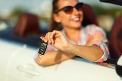 坐在有钥匙的一辆敞篷车汽车的年轻俏丽的妇女 免版税库存照片