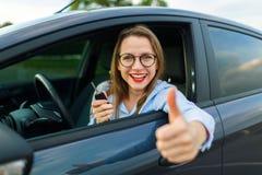 坐在有钥匙的一辆汽车的年轻愉快的妇女在她的手上和 图库摄影