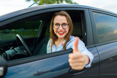 坐在有钥匙的一辆汽车的年轻愉快的妇女在她的手上和 免版税库存照片