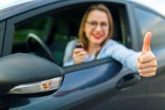 坐在有钥匙的一辆汽车的年轻愉快的妇女在她的手上和 库存图片