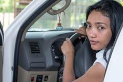 坐在有门户开放主义的一辆汽车的妇女 库存图片