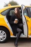 坐在有门户开放主义的黄色出租汽车的美丽的女孩 图库摄影