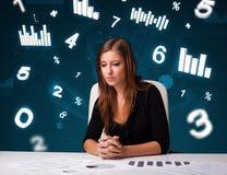 坐在有绘制和统计数据的服务台的新女实业家 免版税库存照片